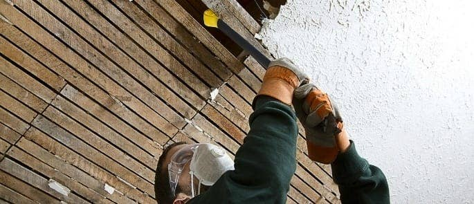 man removing asbestos from a roof with a mask over his face to avoid exposure