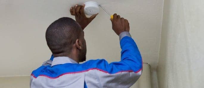 man installing smoke detector for fire safety