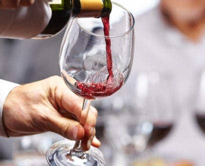 Waiter pouring wine into a wine glass in restaurant