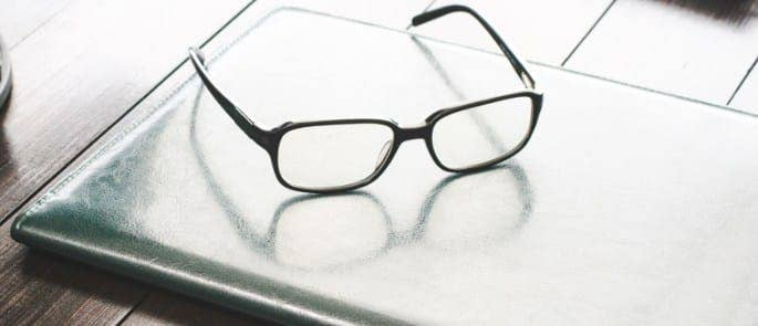 A pair of glasses resting on a desk