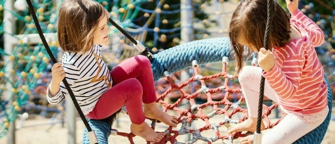 Girls playing on a swing in the park