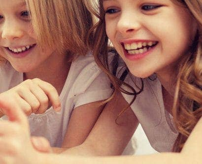 two girls playing on electronic tablet