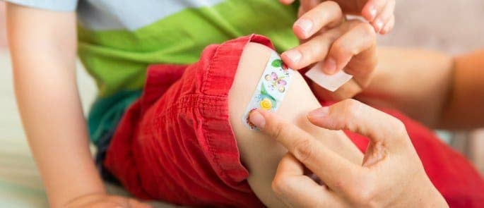 Parent putting a plaster on their child teaching them about first aid
