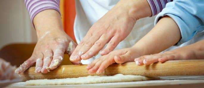 Parent showing child how to roll dough