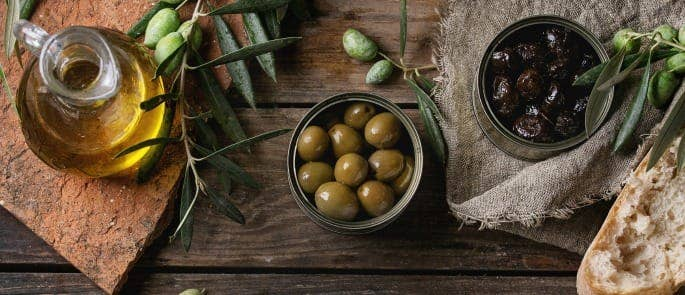 can of olives open with olive oil on the table