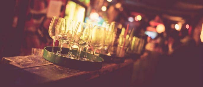 A busy bar with glasses on the wooden counter