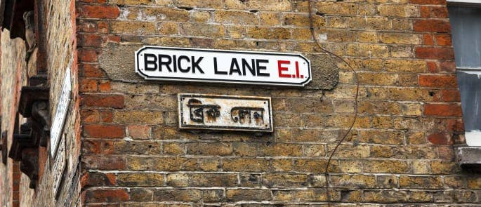 A street sign in Brick Lane, London showing multiple cultural influences