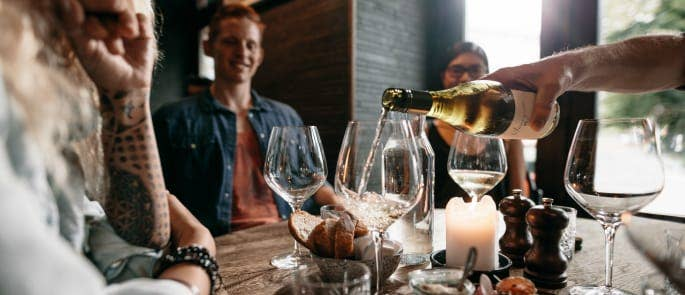 A server pours wine to a table of customers