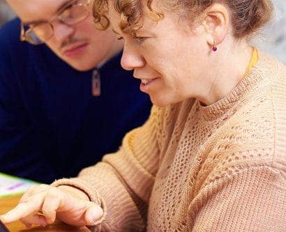carer interacts with service user on tablet device