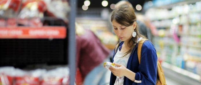 A woman checking the nutrition label on cheese