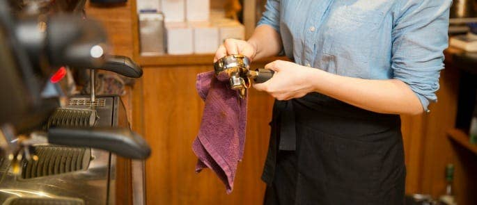 A barista cleaning coffee making equipment as part of a clean as you go policy