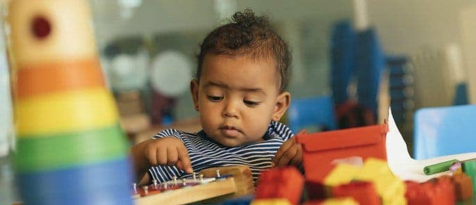 Young child playing with early years toys