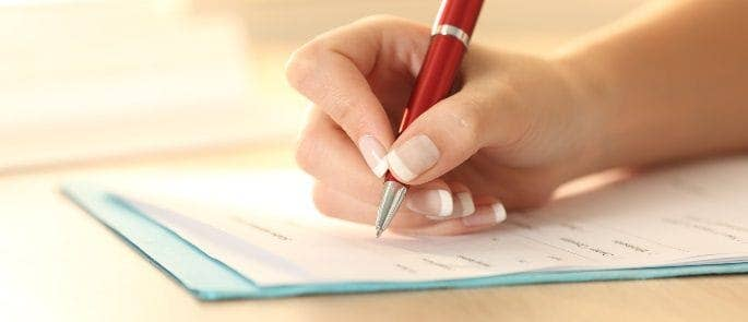 Woman writing a record of a safeguarding concern