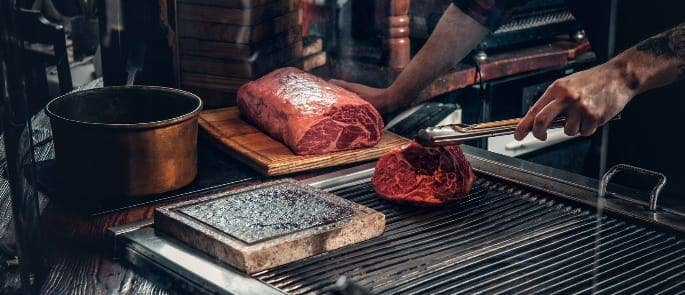 Chef searing and shaving a beef cut