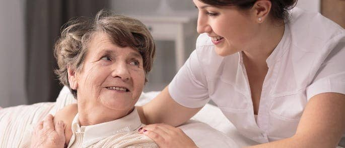 A nurse ensuring her patient is content with their care