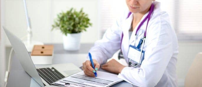 doctor writing a health and social care personal development plan