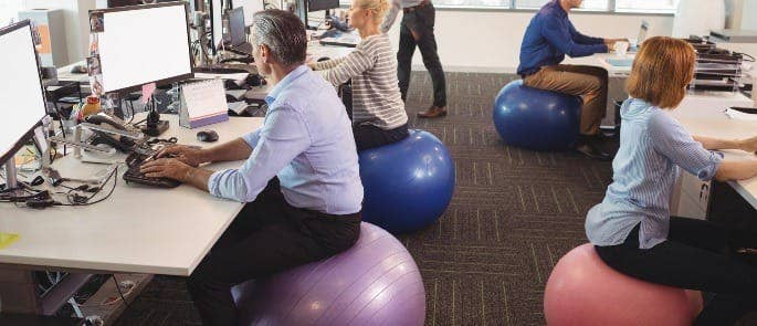 Workers sitting on exercise balls at their desk as part of their wellbeing programme
