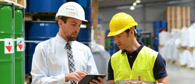 manager delivering feedback to employee in warehouse