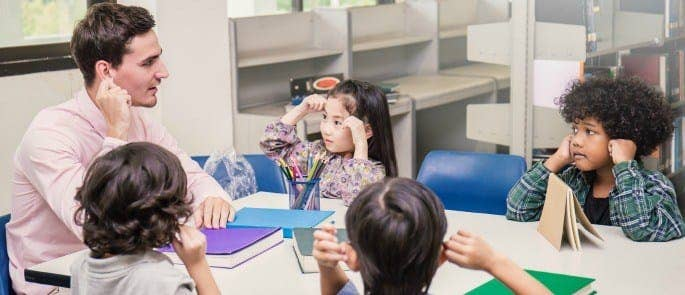 Teacher looking after young students in a classroom