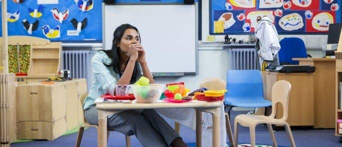 Primary school teacher sat at table thinking about safeguarding concern
