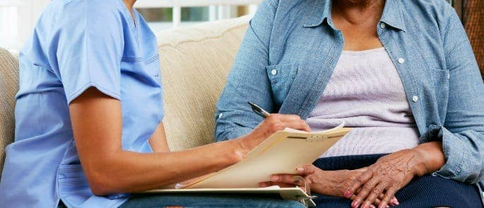 Carer speaking to a patient and taking notes
