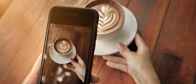 Instagram user taking a photo of a cappuccino to post online