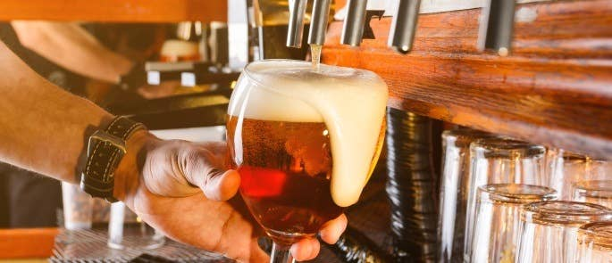 Poor bar techniques can lead to over pouring and a lot of wastage shown with an overflowing pint