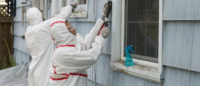 Workers removing lead paint from a building