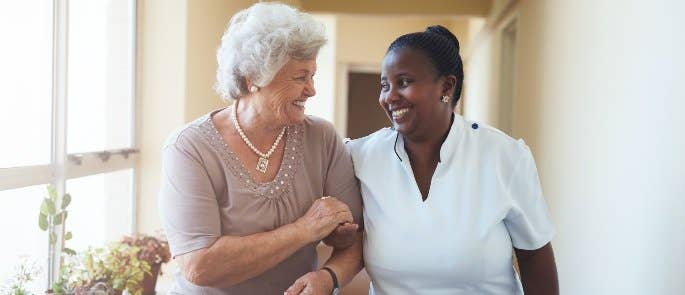 Nurse and patient walking in care home